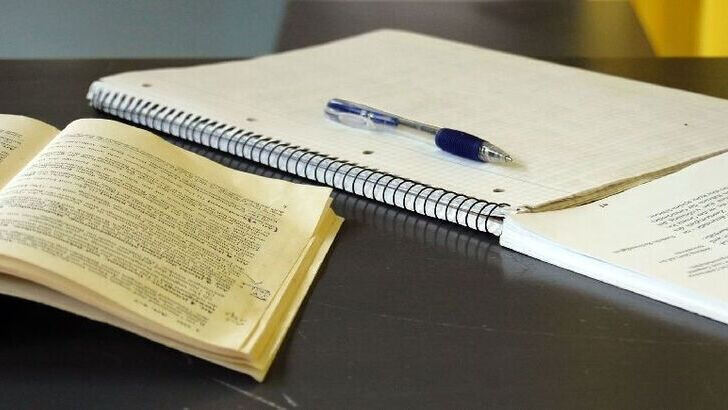 Open Book and spiral-bound notepad with a pen beeing on a table