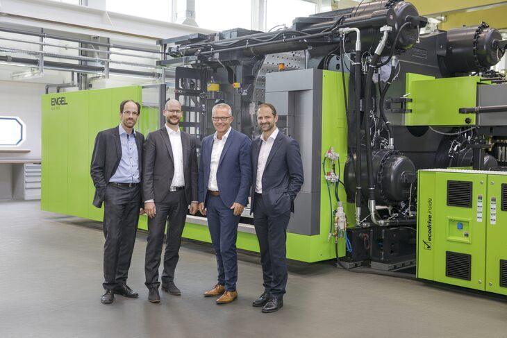 Dr. Norbert Müller, Dr. Michael Emonts, Rolf Saß, Dr. Christoph Steger standing in front of an injection system.